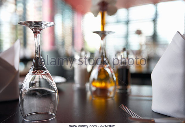 Upside down wine glasses on restaurant table close up surface level focus on foreground - Stock Image