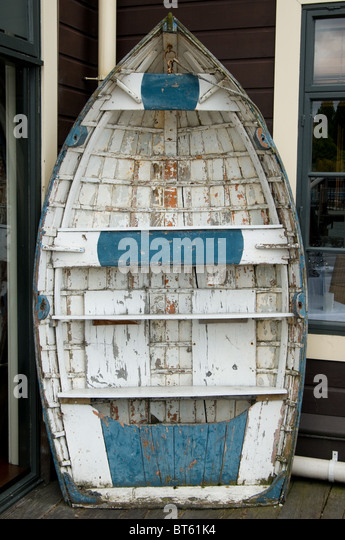 New Zealand blue white rowing boat advertising prop old antique flaking paint upend - Stock Image