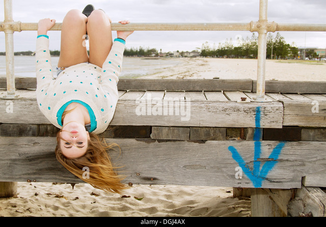 Young woman hanging upside down from pier - Stock-Bilder