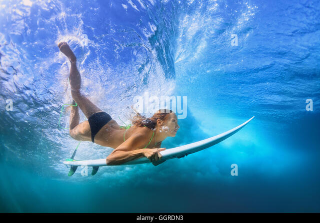 Young active girl in bikini in action - surfer with surf board dive underwater under breaking big ocean wave. school - Stock-Bilder