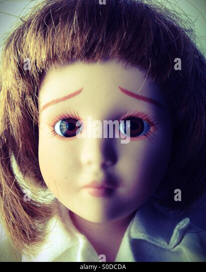 The face of a sad doll. - Stock Image