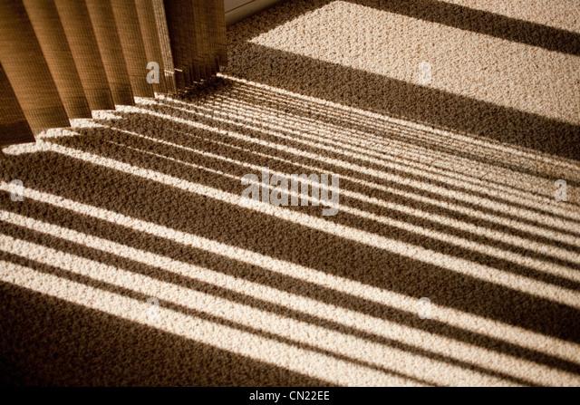 Window blinds casting shadow on carpet - Stock-Bilder