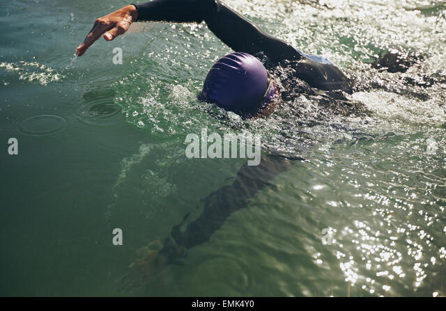 Male swimmer swimming in open water. Athlete practicing for the competition. - Stock Image
