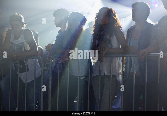 Crowd leaning on railing at concert - Stock Image