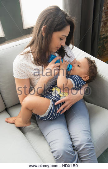 Hispanic mother feeding bottle to baby son on sofa - Stock Image
