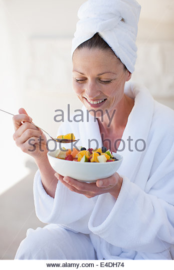 Woman in bathrobe eating bowl of fruit - Stock Image