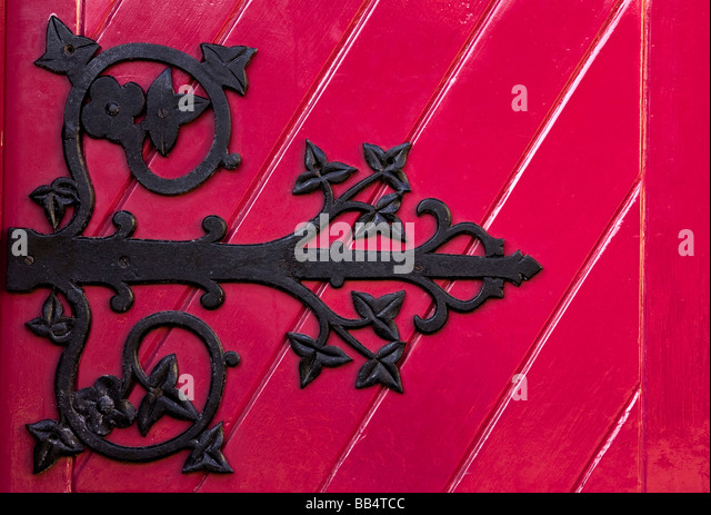 Europe, Ireland, Ennis. A decorative black hinge on a bright red door of the new Franciscan Friary for monastics. - Stock-Bilder