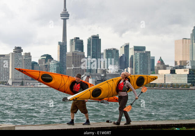 Young couple carry kayaks from Lake Ontario, Toronto waterfront, Toronto, Ontario, Canada. - Stock Image