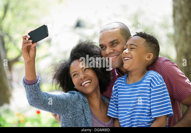 Two adults and a young boy taking photographs with a smart phone. - Stock-Bilder
