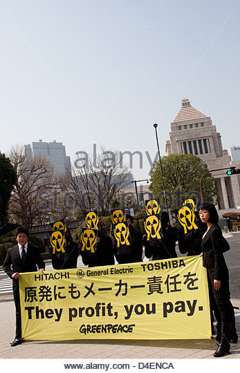 """Greenpeace Japan activists wearing """"nuclear scream"""" masks demonstrate in front of the Japanese parliament. - Stock Image"""
