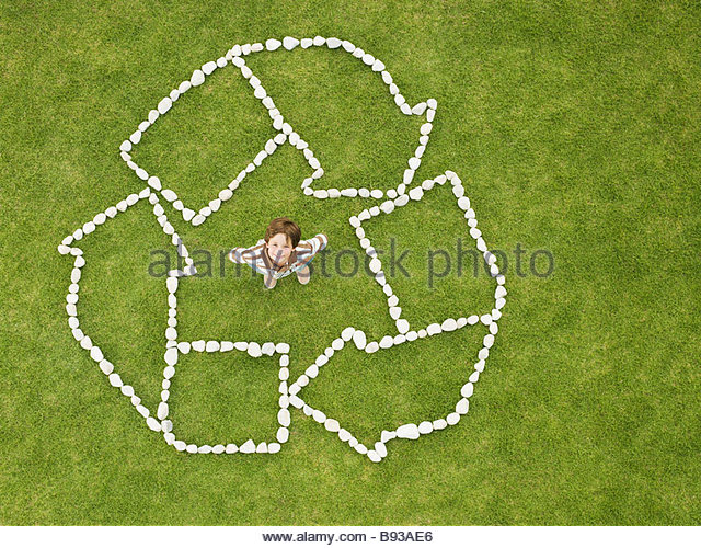 Boy standing in recycling symbol made of rocks - Stock Image