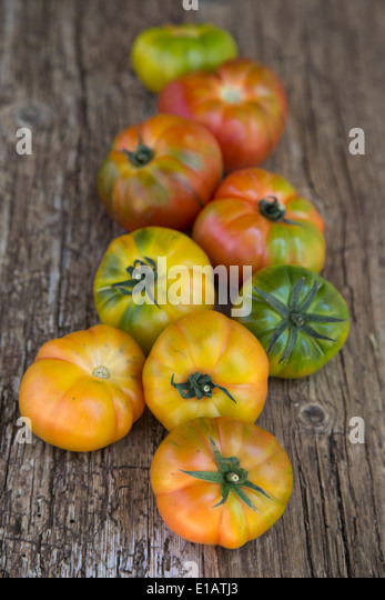 cascading group of Spanish grown Raf striped tomatoes on wooden rustic board - Stock Image