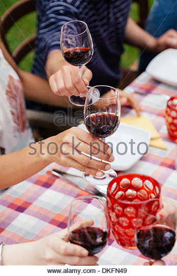 People raising glasses of red wine - Stock Image