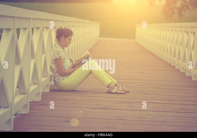 Learning / reading woman concept in sunset - Stock Image