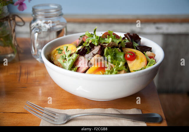 Side view of salad in white bowl with fork, napkin, - Stock-Bilder
