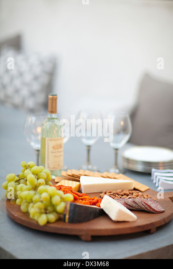 Cheese, crackers, nuts, grapes and salami on wooden cheeseboard next to white wine, tilt - Stock Image