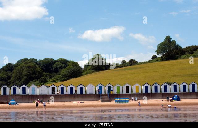 Broadsands beach,Beachhuts and green fields, BOATS, BLUE, SEA, SKY, SEASIDE, SCENE, SEASHORE, BATHERS, COASTAL,Family - Stock Image