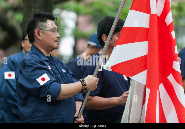 Tokyo, Japan. 15th Aug, 2016. A Japanese nationalist dressed in military uniform holds a war flag of the Imperial - Stock Image