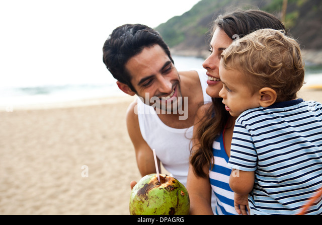 Family on beach with coconut drink - Stock Image