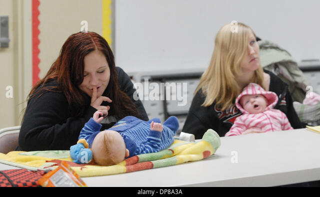 Sixteen year-old Ashley Goble, left, tries to calm her 4 month-old son, Aidan Garner during a teen pregnancy and - Stock Image