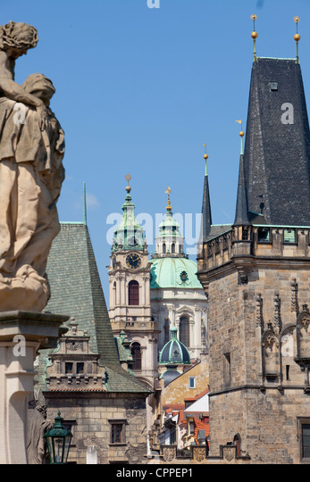 prague - different architectural styles-st. nicolas church and charles bridge tower - Stock Image