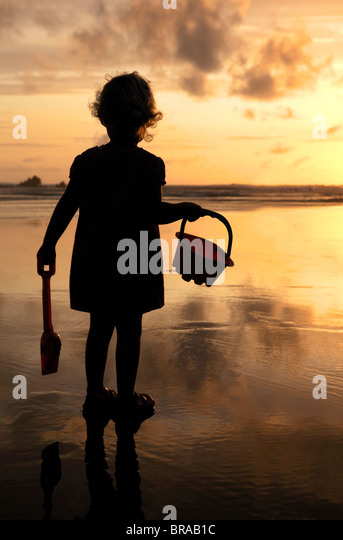 Little girl with bucket and spade silhouetted against setting sun on Summerleaze beach, Bude, UK. - Stock Image