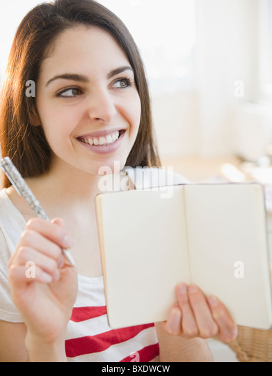 Brunette woman holding an empty notebook - Stock Image