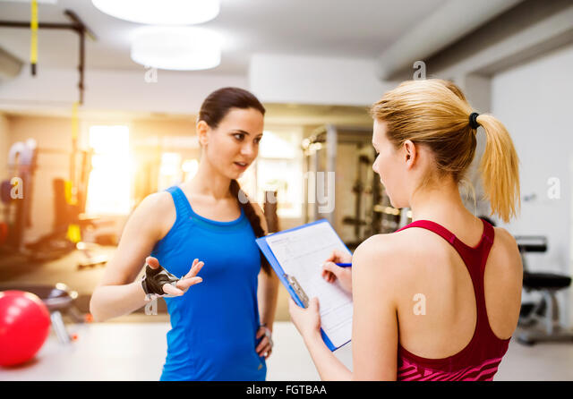 Woman in gym, personal trainer, consultiing plan on clipboard - Stock Image