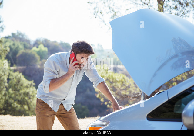 Man talking on cell phone and checking car engine at roadside - Stock Image