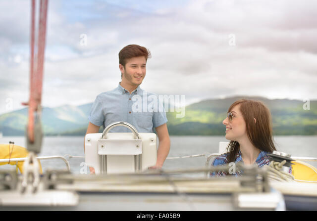 Young couple sailing on yacht over lake - Stock Image