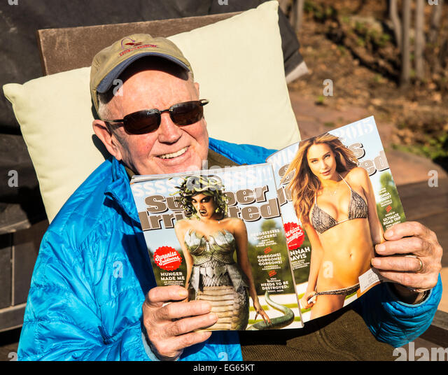 Senior citizen having a good time reading Sports Illustrated Swin Suit Edtion. Boise, Idaho, USA - Stock Image