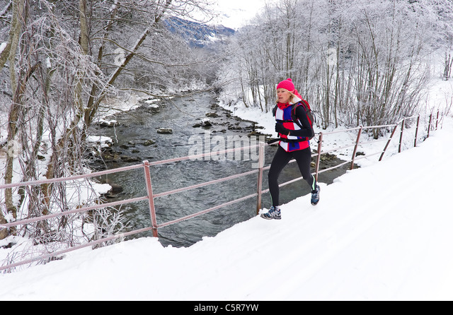 A woman jogging on a bridge over a snowy winter river. - Stock-Bilder