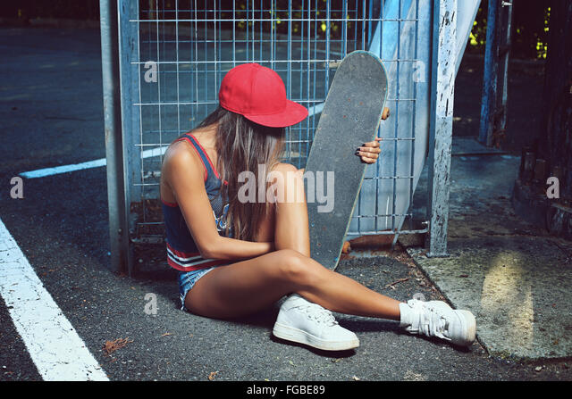 Skater girl seated on the street . Urban shot - Stock Image