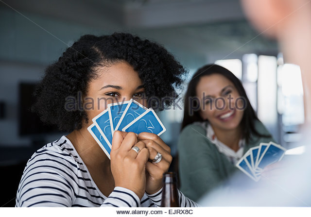 Woman hiding behind playing cards - Stock Image