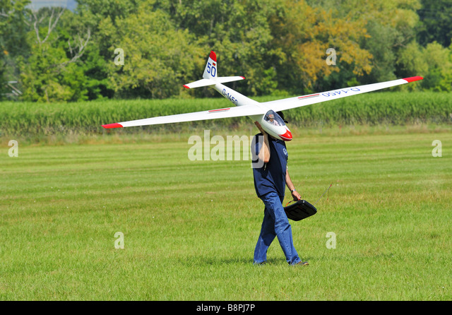 An aeromodeller carrying his model glider across an airstrip - Stock Image