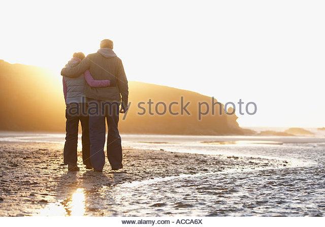 couple happily embracing walking down the beach - Stock-Bilder