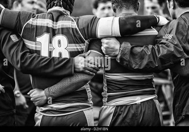 Rugby players huddle after a match - Stock Image