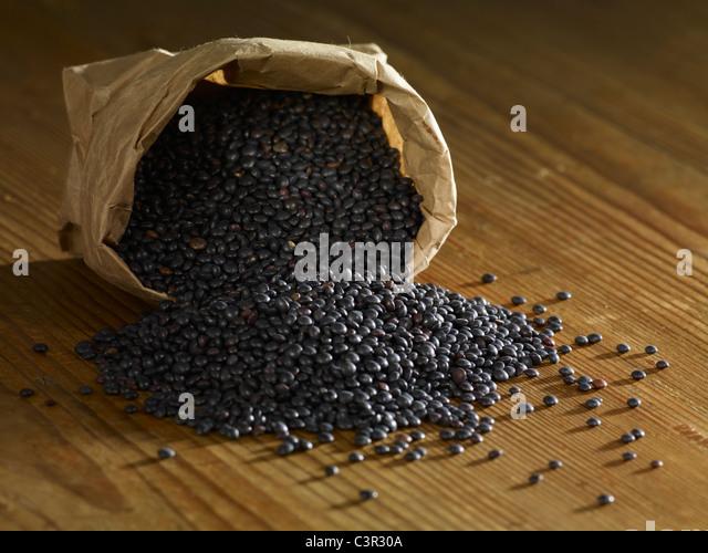Black lentils spilled on wooden surface - Stock Image