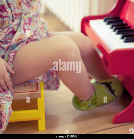 Little girl playing with toy piano, cropped - Stock Image