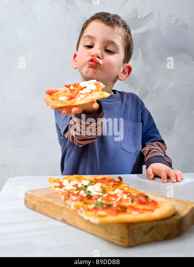 young boy eating homemade pizza - Stock Image