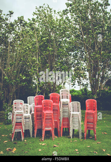 Large stack of plastic chairs in Indonesia. - Stock Image