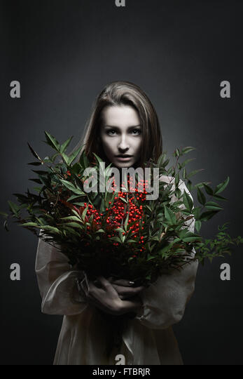 Dark portrait of a beautiful pale woman with bunch of red flowers . Vampire - Stock-Bilder