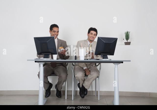 Businessmen eating fast food at desk in office - Stock-Bilder