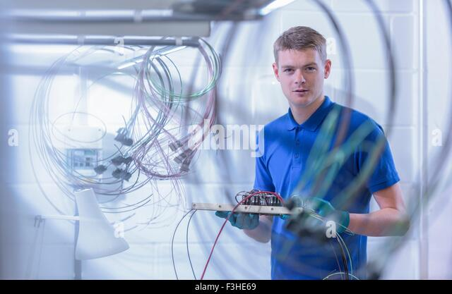 Portrait of apprentice electronics worker in electronics factory, - Stock Image