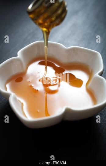 Honey in white bowl - Stock Image