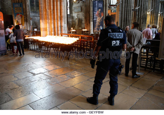 A French policeman stands guard as people attend a mass to pay tribute to French priest Father Jacques Hamel at - Stock-Bilder