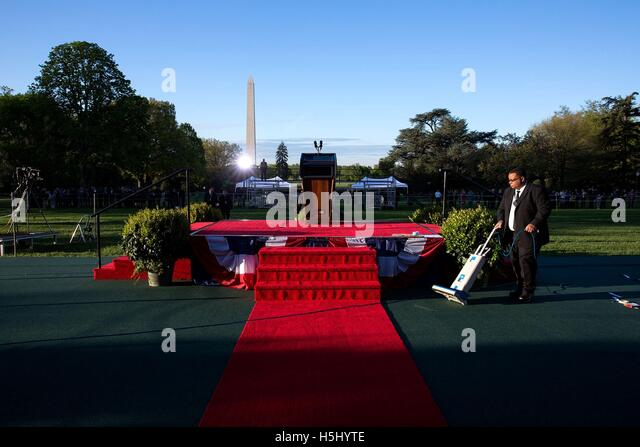 A White House employee vacuums the red carpet as final preparations are made for the State Arrival ceremony for - Stock Image