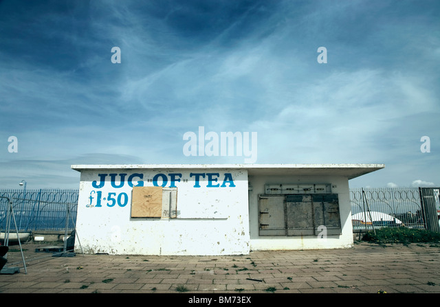 architecture image of a small closed down café building with slogan jug of tea on the front on a sunny day - Stock-Bilder