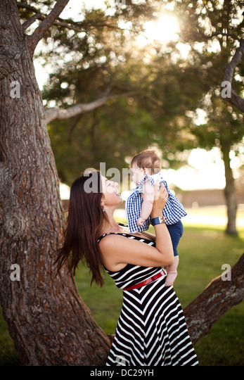 Portrait of mother holding baby daughter - Stock Image