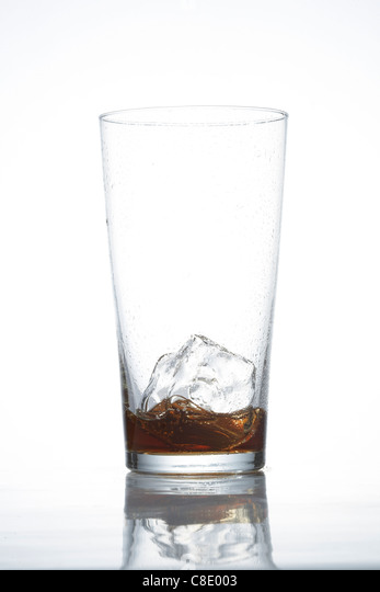 Empty glass of cola with ice cube - Stock Image
